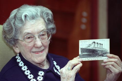 EVA HART SURVIVOR OF THE SINKING OF THE TITANIC DISPLAYS A POSTCARD OF THE SHIP IN LONDON.