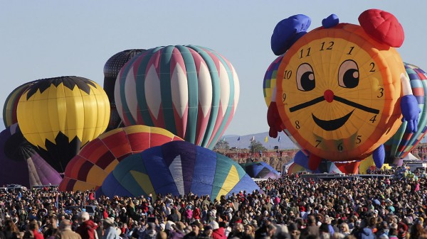 Hot air balloons, one of them shaped like a clock, are prepared before taking flight during the 42nd annual Albuquerque International Balloon Fiesta in Albuquerque, New Mexico