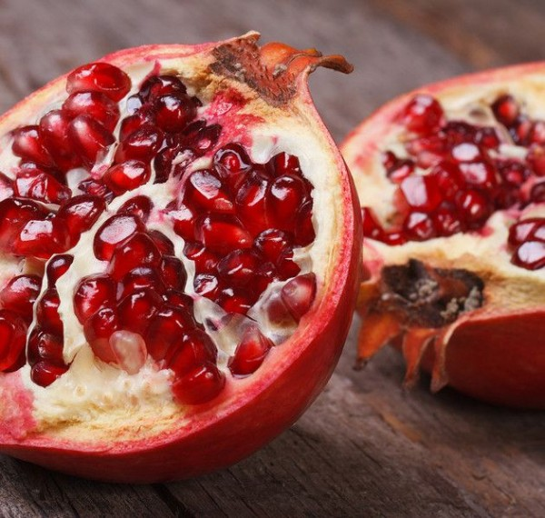 cut ripe pomegranate on an old wooden table closeup. horizontally