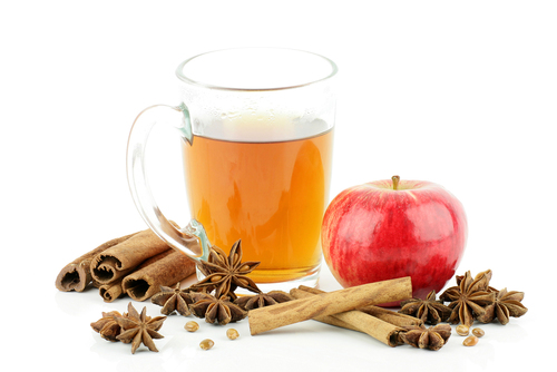 A glass of tea with apple and spices,on a white background.
