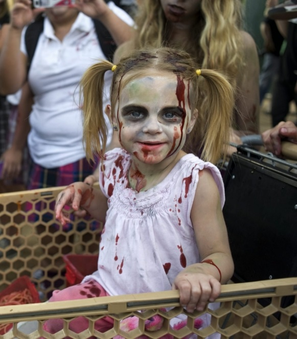 epa03795399 A young girl is pushed in a shopping cart with fake body parts during a zombie walk through downtown San Diego during the Comic Con 2013 in San Diego, California, USA, 20 July 2013. Comic-Con International San Diego began in 1970 when a group of comics, movie and science fiction fans banded together to put on the first comic book convention in southern California. EPA/DAVID MAUNG